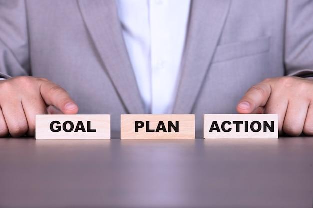 Obiettivo, piano, azione, scala del successo, le parole sono scritte su blocchi di legno