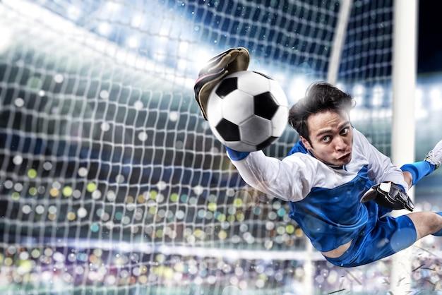 Il portiere prende la palla nello stadio durante una partita di calcio.