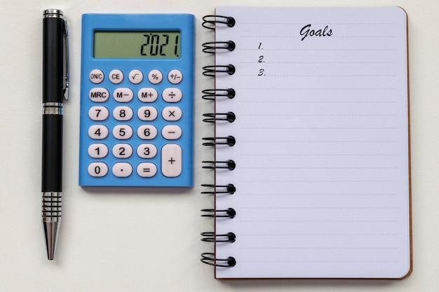 Obiettivi per il 2021, calcolatrice, penna e blocco note. risoluzione del nuovo anno