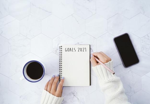 Obiettivi 2021 sulla disposizione piana della donna che scrive sul taccuino e che beve tazza di caffè calda e utilizza lo smartphone su fondo di marmo bianco con lo spazio della copia, concetto di risoluzioni del nuovo anno