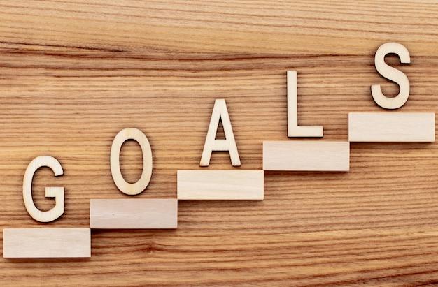 Concetto di obiettivi con scala di successo sulla tavola di legno.