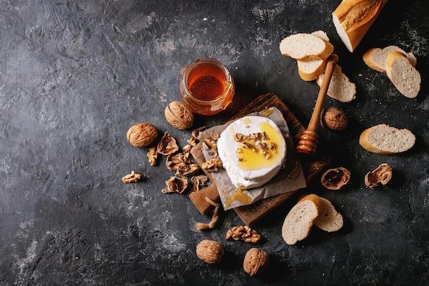 Formaggio di capra servito con miele e noci su sfondo nero trama. vista dall'alto, piatto. copia spazio