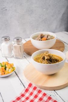 Curry di capra su una ciotola bianca servito con zuppa di capra