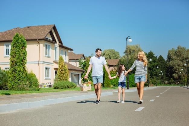 Andando per l'avventura. piacevole giovane famiglia che va a fare un picnic nella foresta, tenendosi per mano e sorridendo felice mentre l'uomo porta un cesto con il cibo