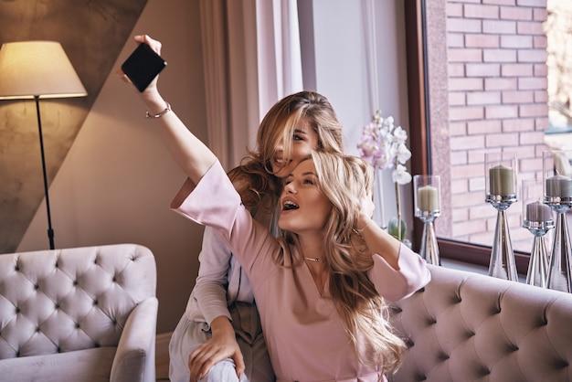 Impazzendo. giovani donne attraenti in abiti eleganti che si fanno selfie e sorridono mentre sono sedute sul divano
