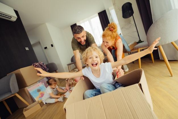 Andando avanti. uomo felice positivo che spinge la scatola di cartone con suo figlio dentro divertendosi