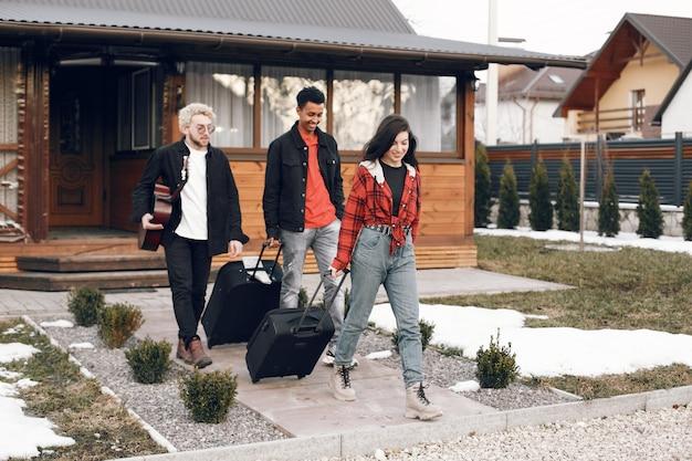 Partire per un viaggio. giovani amici che escono di casa con i bagagli. concetto di viaggio.