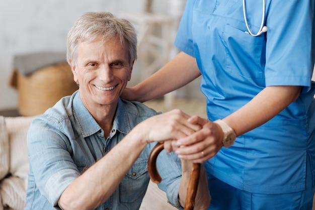 Non affrontarlo da solo. uomo anziano vivace e affascinante che ha un visitatore dall'ospedale che esegue un controllo settimanale su di lui e lo aiuta a stare meglio