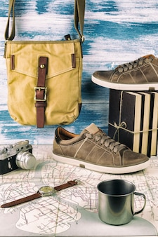 Partire per un viaggio: una grande vecchia carta, una borsa a vita bassa, scarpe da ginnastica, tre libri, una macchina fotografica retrò, una tazza e un orologio da polso.