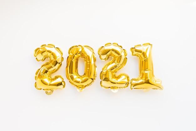 Aerostati della stagnola del nuovo anno dell'aria dell'oro sotto forma di numeri 2021 sulla superficie bianca