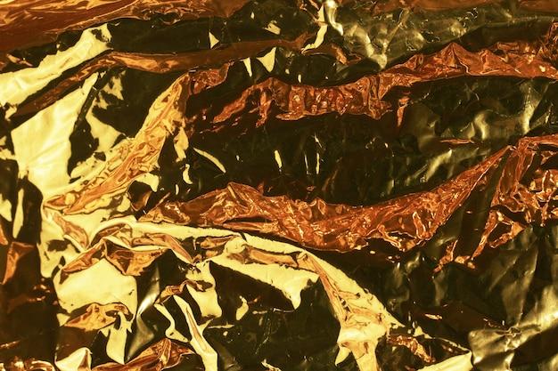 Fondo oro. texture di colore metallico stropicciato giallo o oro con luce dura. lamina con pieghe in primo piano.