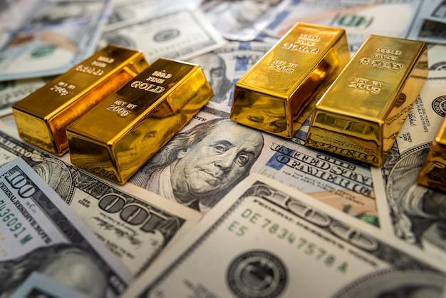 Lingotto d'oro su banconote da 100 dollari. investimento