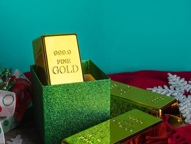 Lingotti d'oro come regalo di natale sulla tavola di legno con ornamenti.