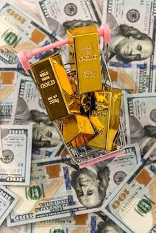 I lingotti d'oro si trovano in un carrello della spesa, sfondo con dollari. concetto di denaro, ricchezza e abbondanza