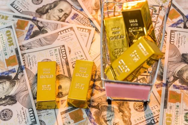 I lingotti d'oro giacciono in un carrello della spesa, sfondo con dollari