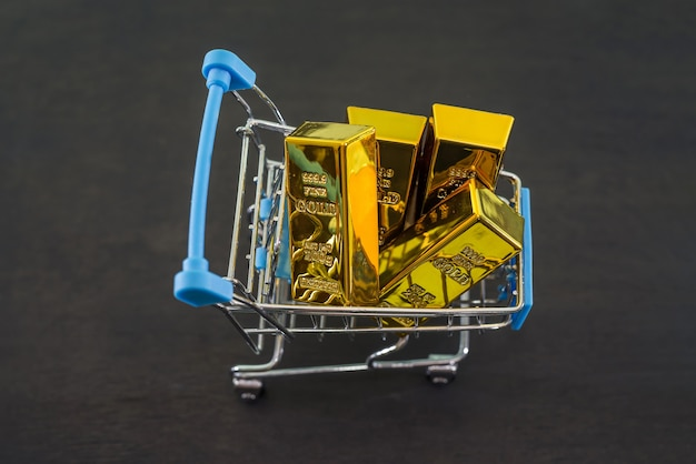 Lingotti d'oro in un carrello su un tavolo di legno nero. vista dall'alto.