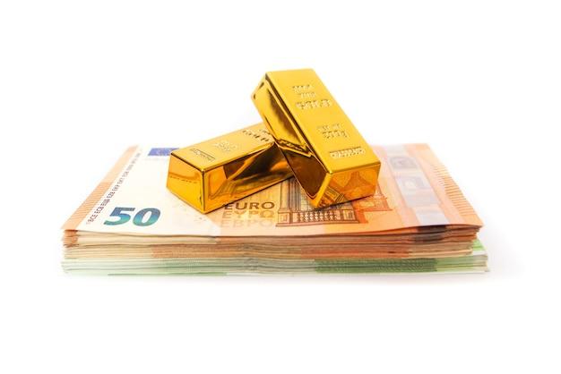 Lingotti d'oro su una pila con euro su una superficie bianca.