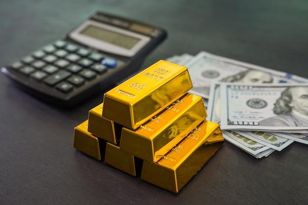 Lingotti d'oro con dollari e una calcolatrice su un tavolo di legno nero.