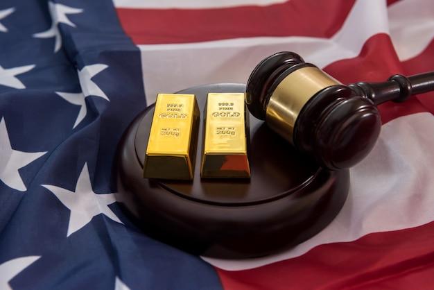 Lingotti d'oro con martelletto che si trova sulla bandiera degli stati uniti Foto Premium