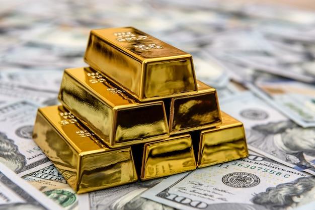 Lingotti d'oro con banconote da cento dollari come sfondo