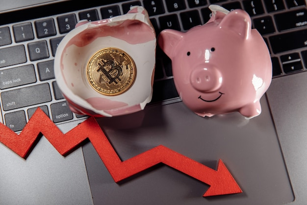 Oro bitcoin rotto salvadanaio e freccia giù sul laptop la caduta del valore di bitcoin laptop