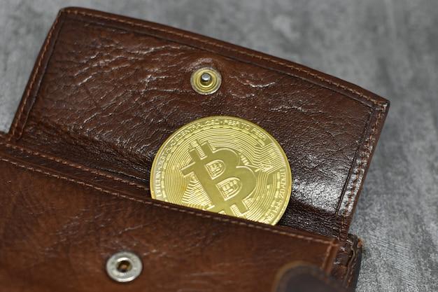 La moneta bitcoin d'oro si trova nella tasca della borsa, primo piano. criptovaluta nel portafoglio