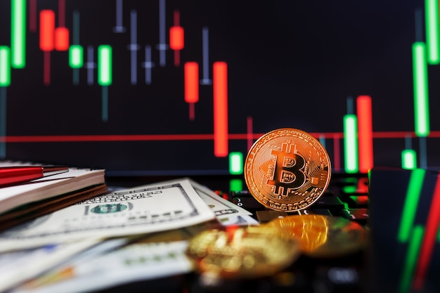 Bitcoin dell'oro sul primo piano dei grafici di affari e sulle banconote da 100 dollari.