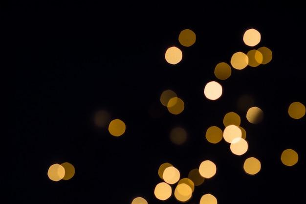 Le luci del bokeh dell'oro brillano. sfondo festivo nero.
