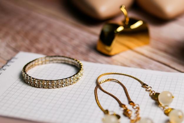 Il braccialetto d'oro si trova su un taccuino vuoto, lista per la sposa, obiettivi, programma del matrimonio.