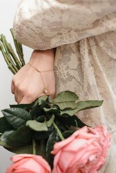 Bracciale in oro con una perla in mano alla ragazza. una ragazza in un abito di pizzo tiene in mano un mazzo di peonie con un braccialetto alla moda.
