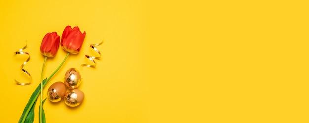 Uova di pasqua marroni dell'oro con i tulps rossi su fondo giallo