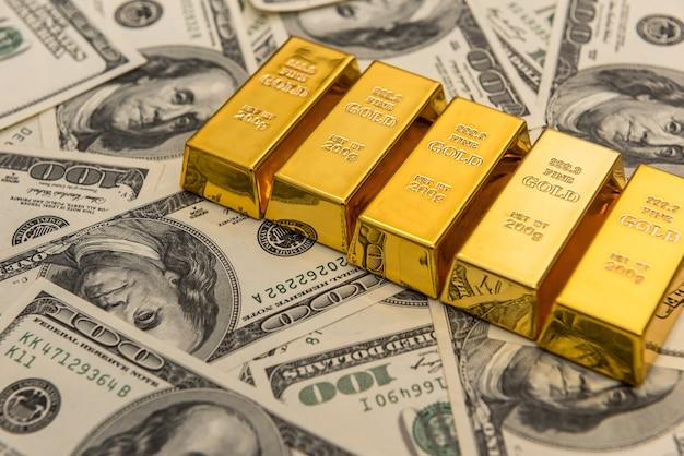 Lingotti d'oro e 100 banconote in denaro americano