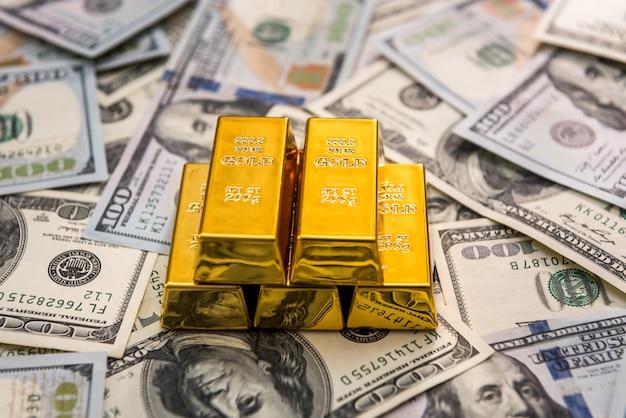 Lingotti d'oro alle banconote in dollari americani da vicino