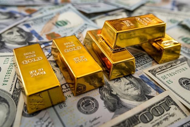 Lingotti d'oro sul mucchio di banconote da un dollaro americano