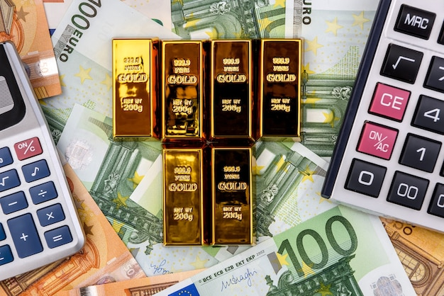 Lingotti d'oro con calcolatrice sulle banconote in euro