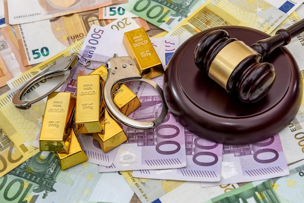 Lingotti d'oro con martelletto del giudice e manette sulle banconote in euro