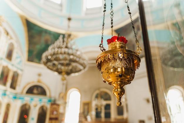 Incensiere d'oro con un candeliere rosso nella chiesa