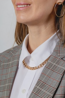 Accessorio catena d'oro con camicia bianca e giacca in stile donna d'affari