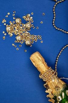 Bottiglia di champagne oro con coriandoli dorati su sfondo di carta blu