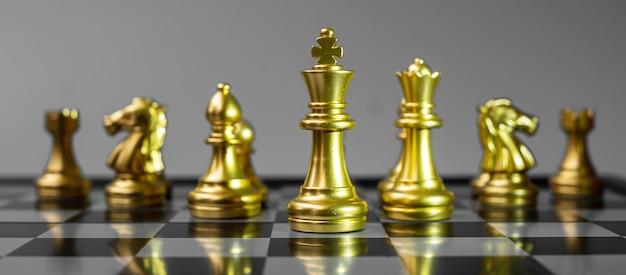 Gold chess figure team (re, regina, alfiere, cavaliere, torre e pedone) sulla scacchiera contro l'avversario durante la battaglia.