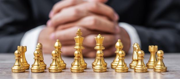 Squadra di figure di scacchi d'oro (re, regina, vescovo, cavaliere, torre e pedone) con sfondo di manager di uomo d'affari.