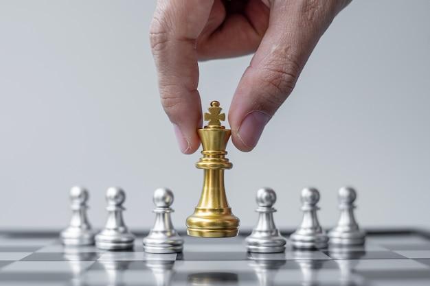 Figura del re degli scacchi d'oro distinguiti dalla massa sullo sfondo della scacchiera.