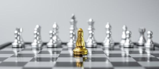 Gold chess knight figura sulla scacchiera contro avversario o nemico.