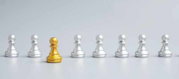 Figura gold chess pawn distinguiti dalla folla sullo sfondo della scacchiera. strategia, leadership, affari, lavoro di squadra, diverso, unico e concetto di gestione delle risorse umane