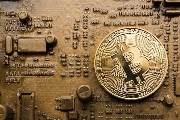 Bitcoin moneta d'oro sulla scheda madre dorata