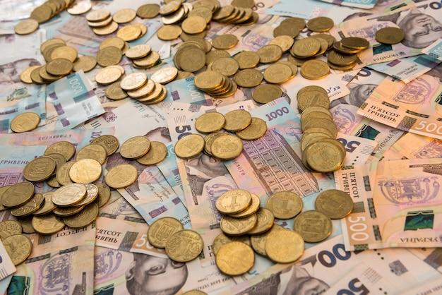 Le monete d'oro giacciono sulle banconote. uah. soldi ucraini. concetto di denaro e risparmio.