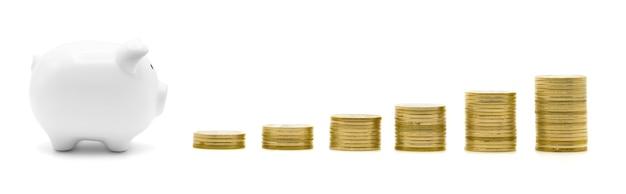 Pila di monete d'oro e piggy isolato su bianco con crescita concetto di finanza aziendale per risparmiare denaro