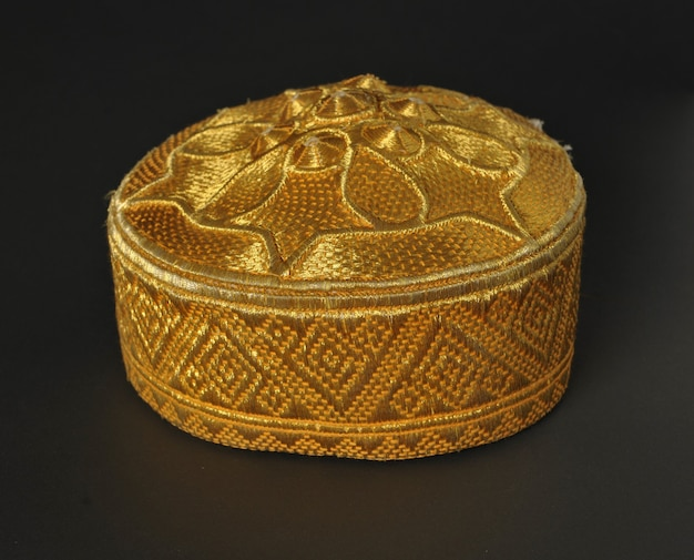 Cappellino zucchetto asiatico tradizionale color oro su sfondo scuro