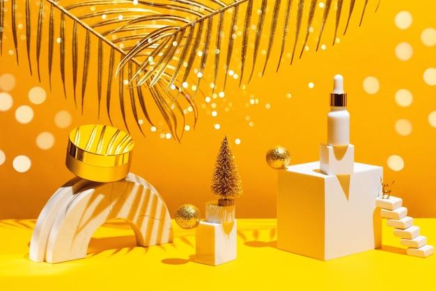 Composizione in oro con crema e siero, forme geometriche e albero di natale, su una parete gialla con foglie di palma, concetto di bellezza e cosmetici.
