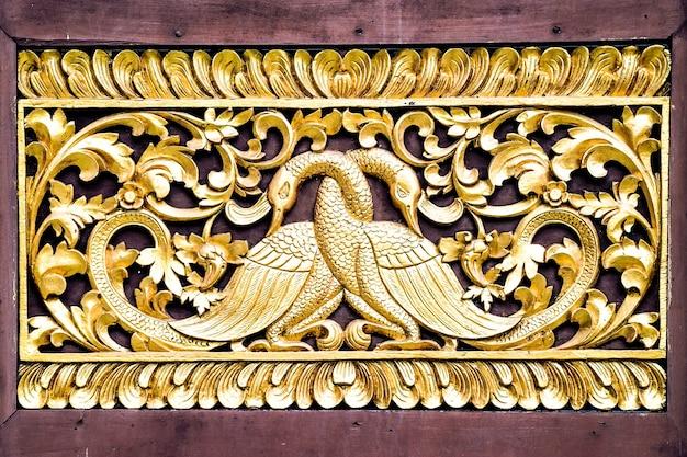Coppia d'oro cigno arte artigianale realizzata a mano da artisti asiatici thailandesi, installazione sul muro del tempio thailandese.